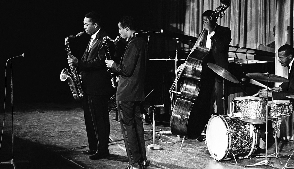 Photo of John Coltrane performing with his band.