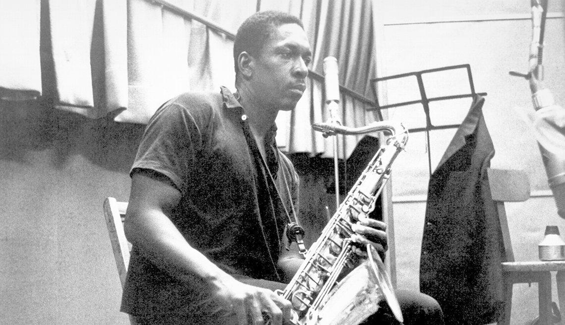 Photograph of John Coltrane recording in the studio around 1958.