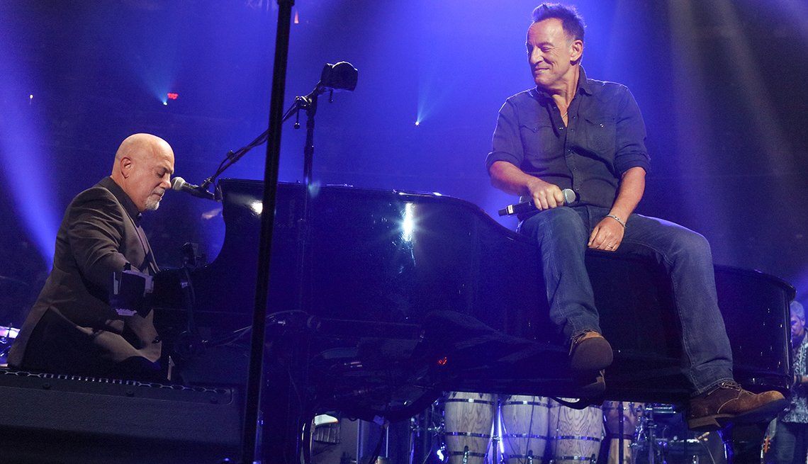 Billy Joel playing the piano as Bruce Springsteen sits on top.