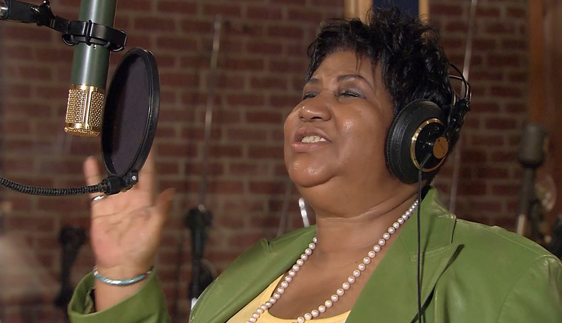 Aretha Franklin singing in front of a microphone.