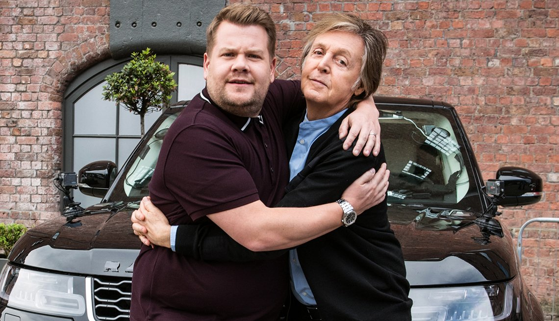 Paul McCartney and James Corden hugging in front of a car.