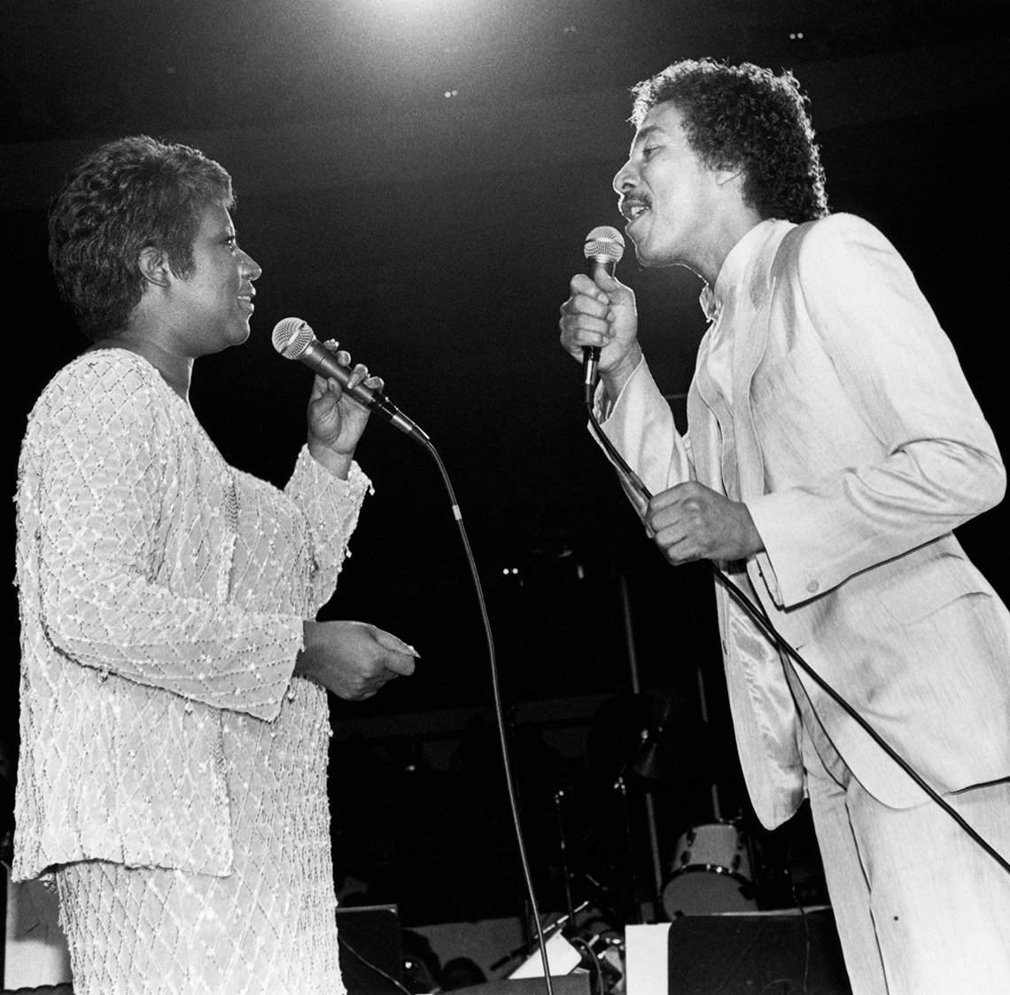 Aretha Franklin signing on stage with Smokey Robinson