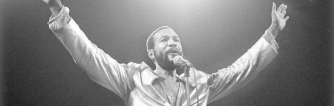Marvin Gaye with his hands in the air singing.