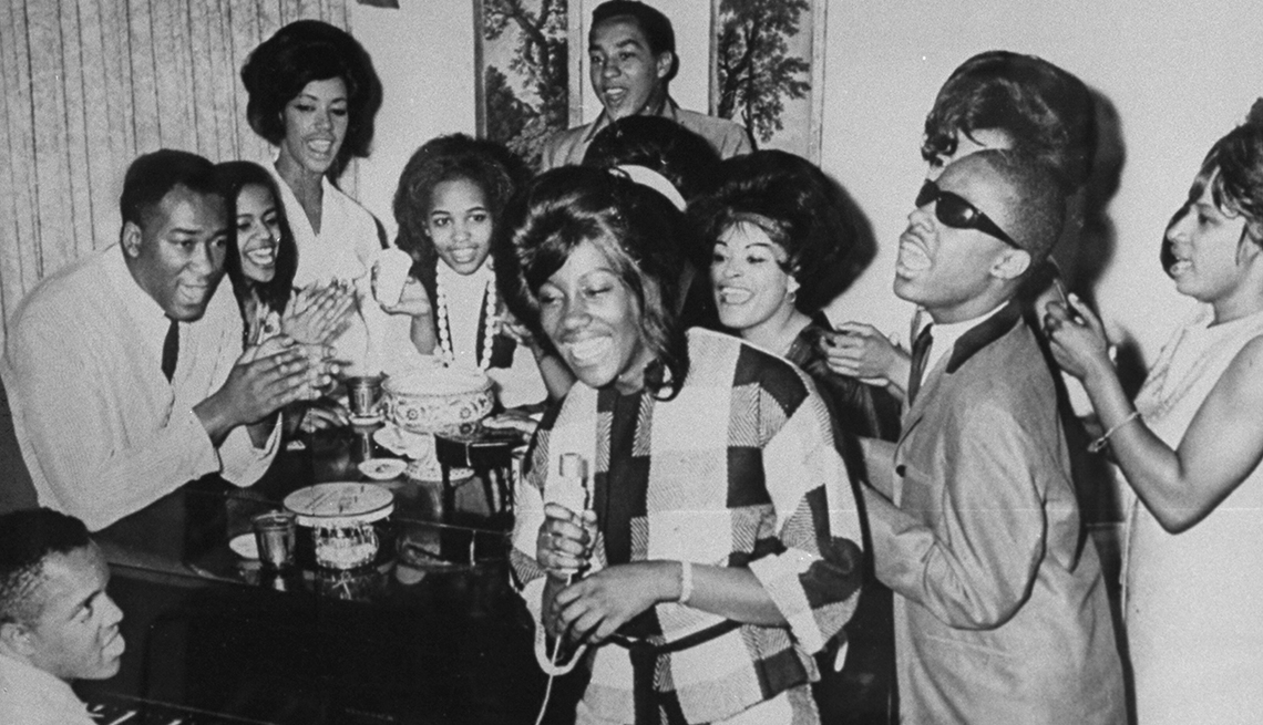 Berry Gordy and a group performing around a piano.
