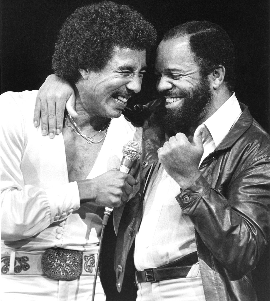 Berry Gordy with his arm around Smokey Robinson on stage.