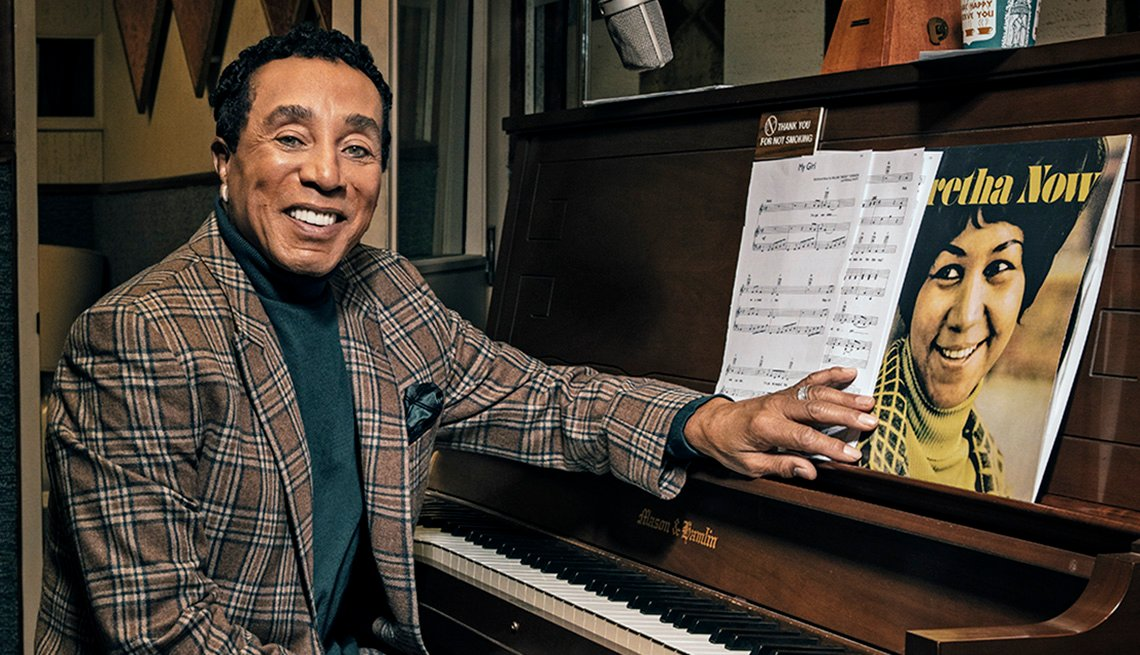 Smokey Robinson sitting in front of a piano