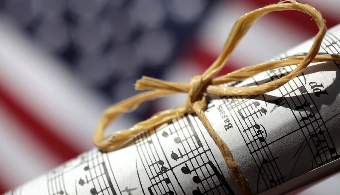 Partitura amarrada con un lazo y al fondo una bandera de Estados Unidos