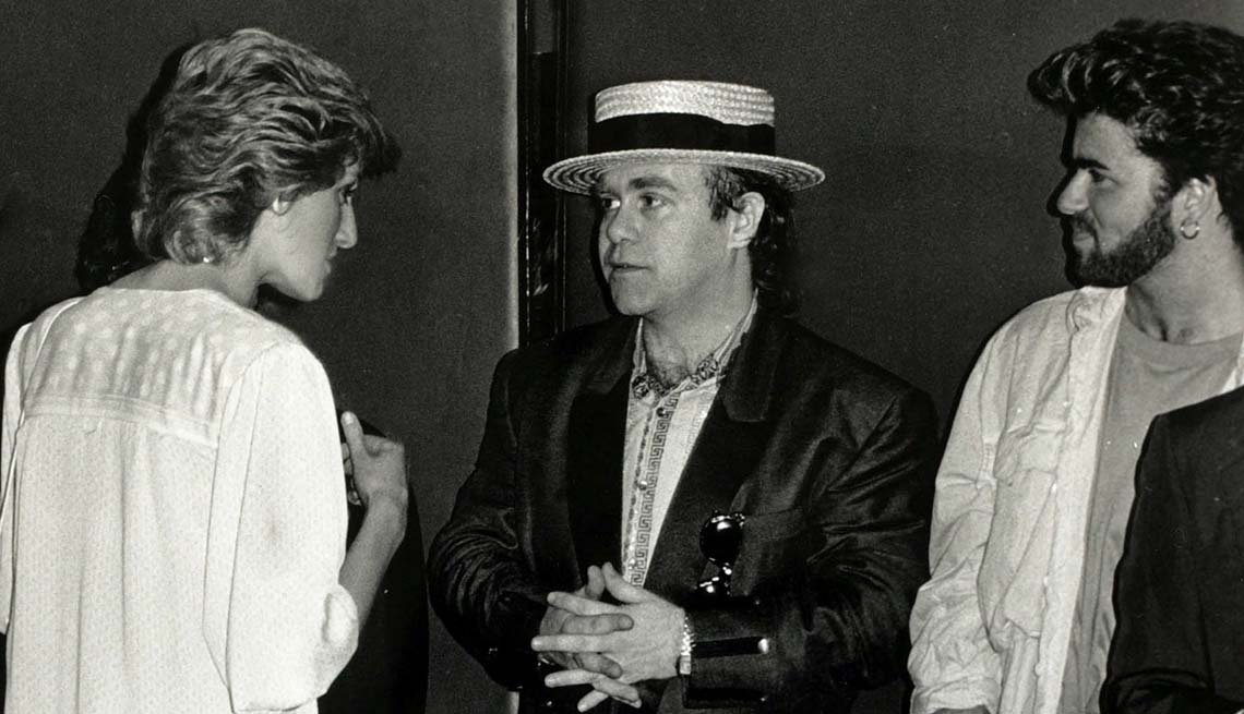 """item 4 of Gallery image - Diana, Princess of Wales pictured chatting to musicians Elton John (centre) and George Michael at the """"Feed the World"""" Live Aid concert at Wembley, July 1985."""
