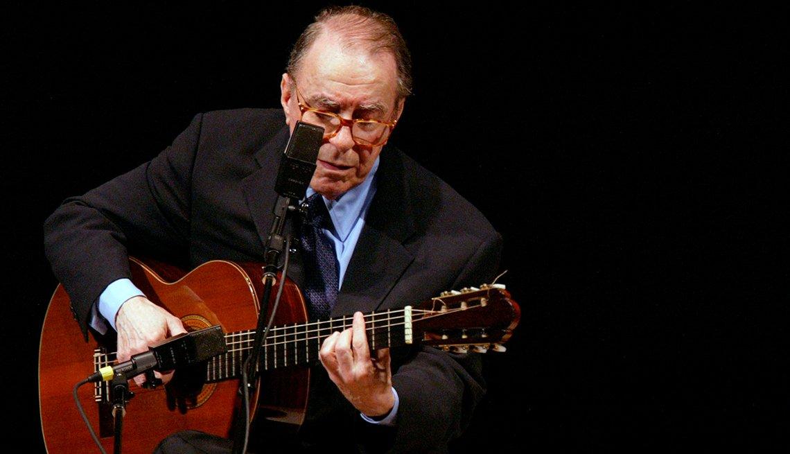 Joao Gilberto en un escenario con una guitarra.