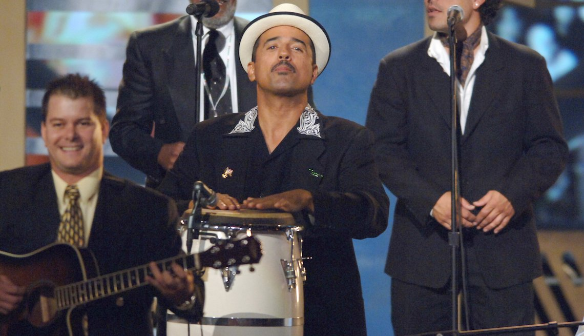 John Santos (C) performs