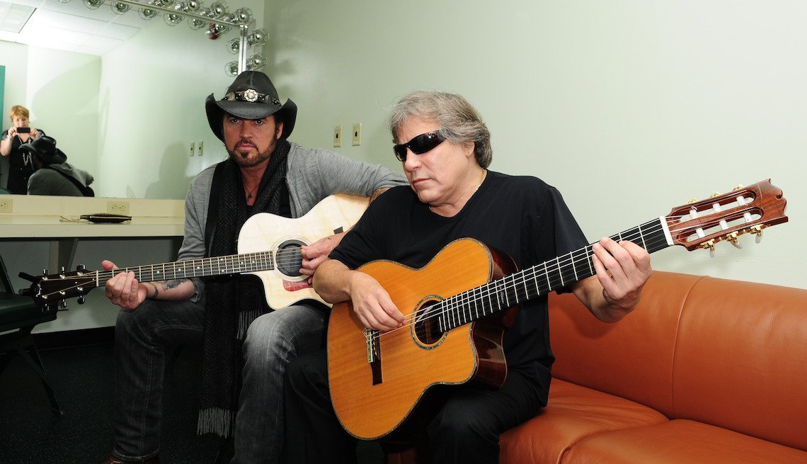 item 2, Gallery image. Billy Ray Cyrus and Jose Feliciano backstage inside the dressing room break out into a acoustic jamming session at the Miami Rocks Our Troops at Bank United Center on September 29, 2012 in Miami, Florida.