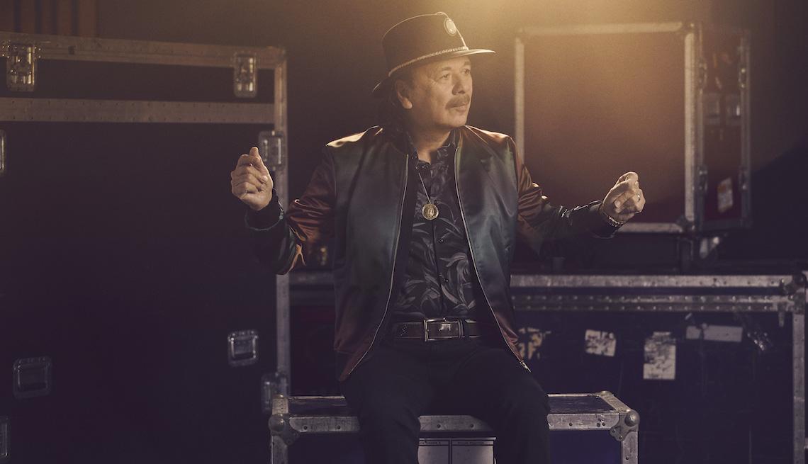 Carlos Santana sentado sobre cajas de equipo musical y tronando sus dedos en el aire.