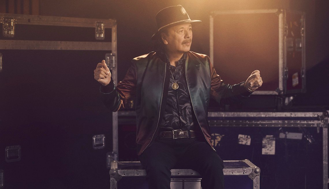 Carlos Santana snapping his fingers while sitting on music equipment crates