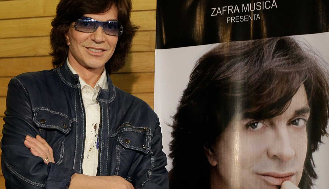 Camilo Sesto al lado de un afiche de promoción