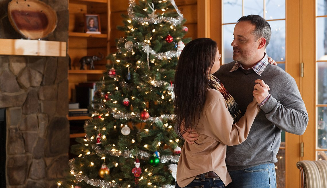 a mature couple dances in their living room in front of a fireplace and a decorated christmas tree