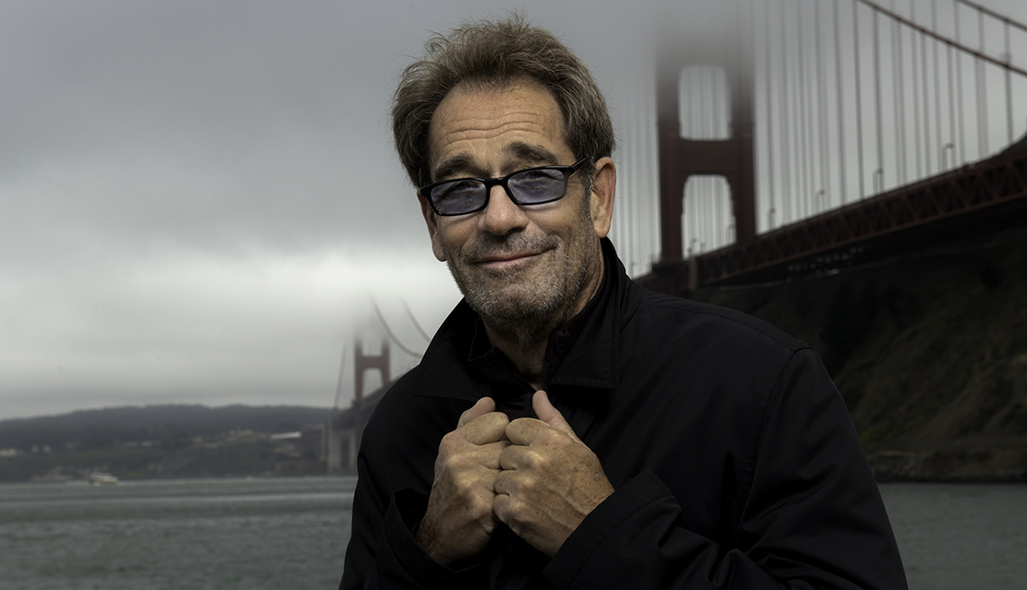Singer Huey Lewis standing nearby San Francisco's Golden Gate Bridge on a foggy day