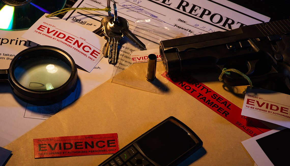 A desk with evidence from a crime case that includes a gun blank photos crime scene information sheet c d, magnifying glass keys cell phone bullet shell and police reports