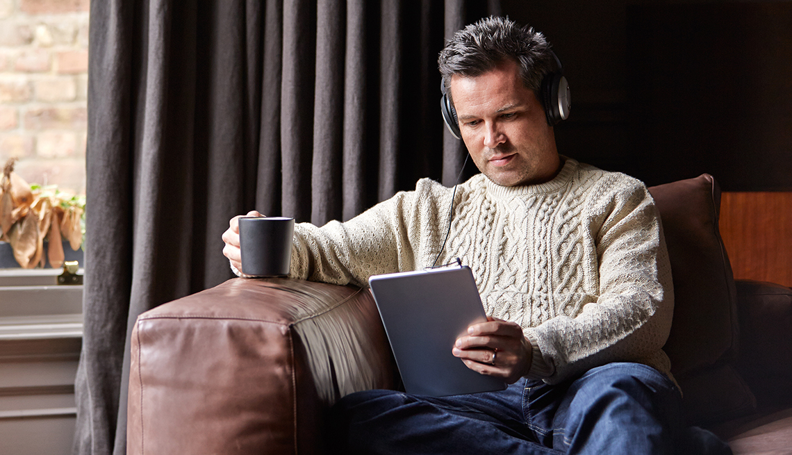 A man sitting on a sofa listening to audio on headphones while holding a coffee mug