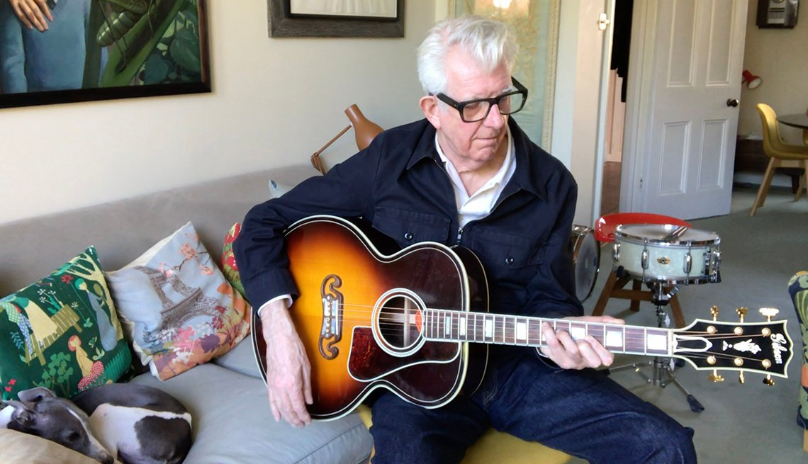 Singer songwriter Nick Lowe playing the guitar at home