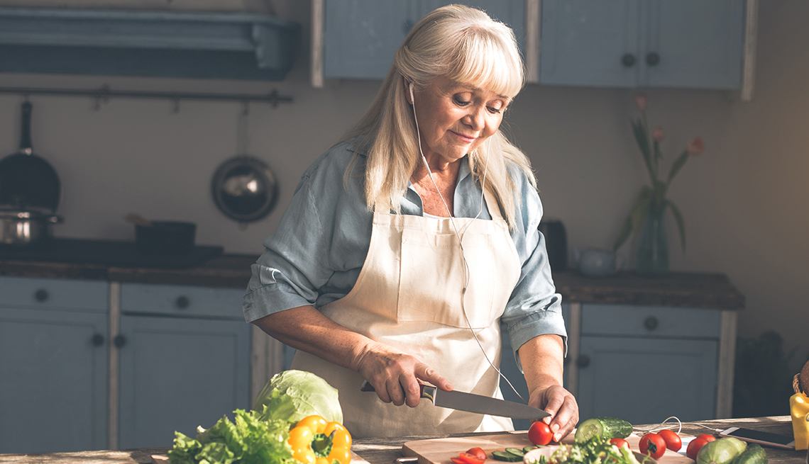 A woman cutting vegetables in the kitchen while wearing headphones