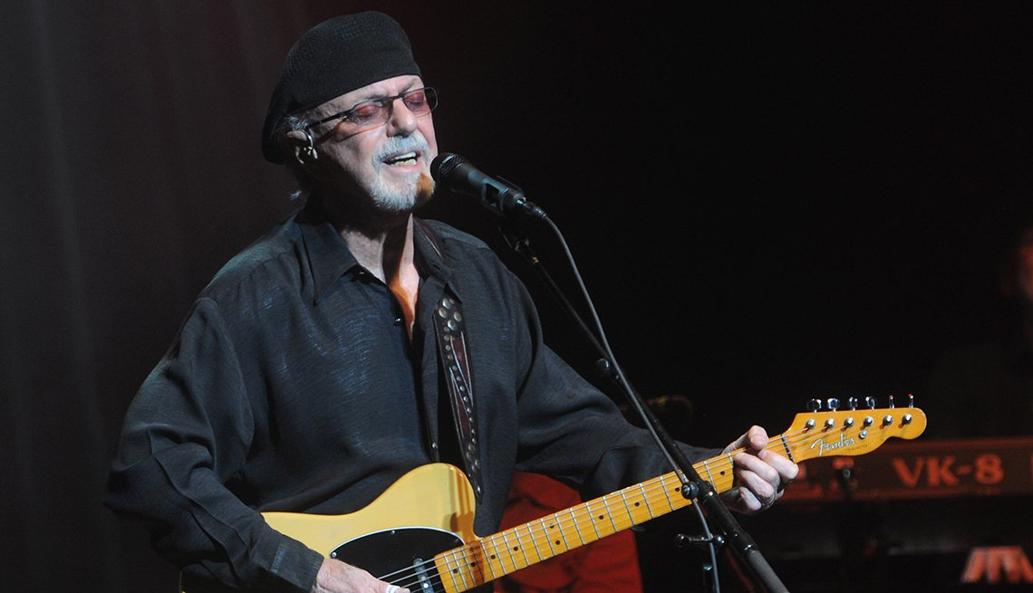 Dion Dimucci playing a guitar as he performs at St. George Theatre in New York City