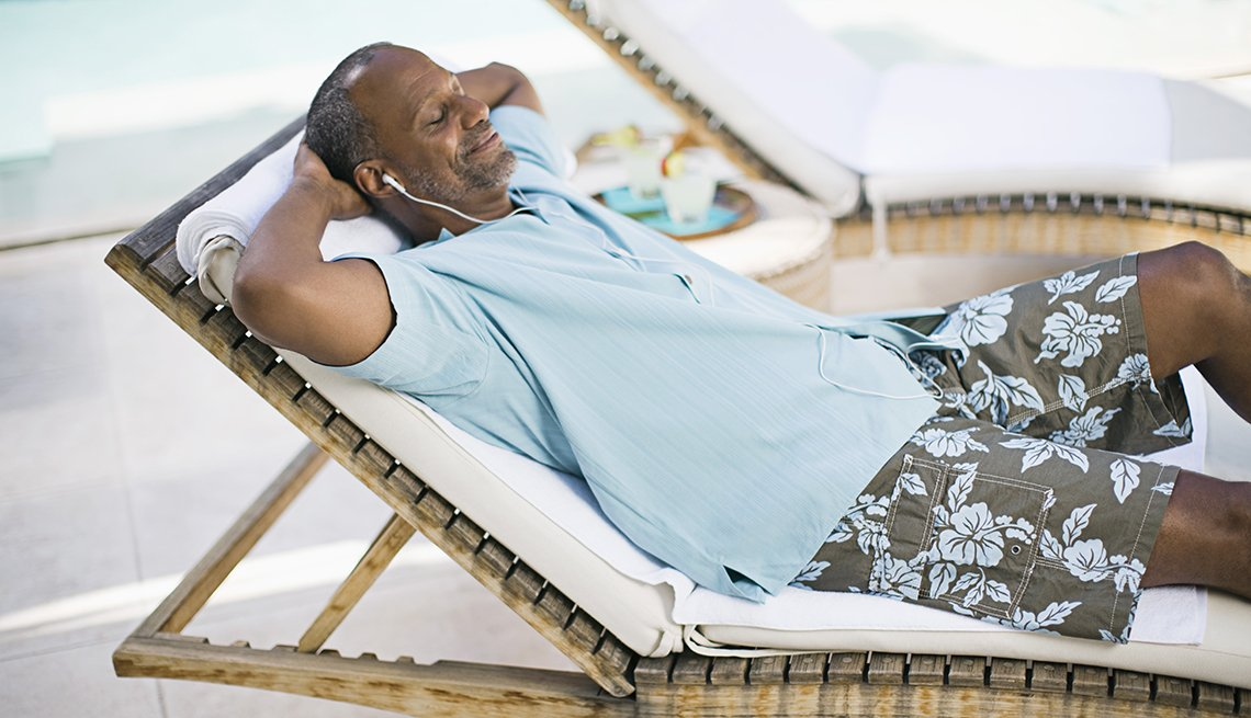 A man lying on a pool chair relaxing while wearing headphones listening to music