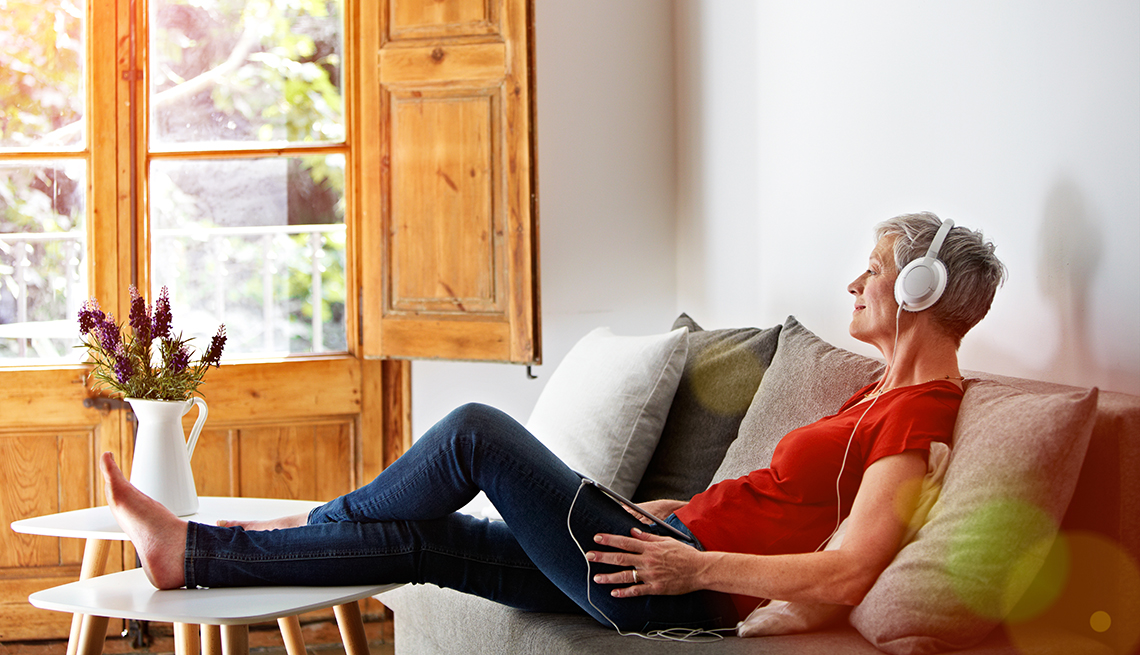 A woman sitting on her sofa listening to a podcast