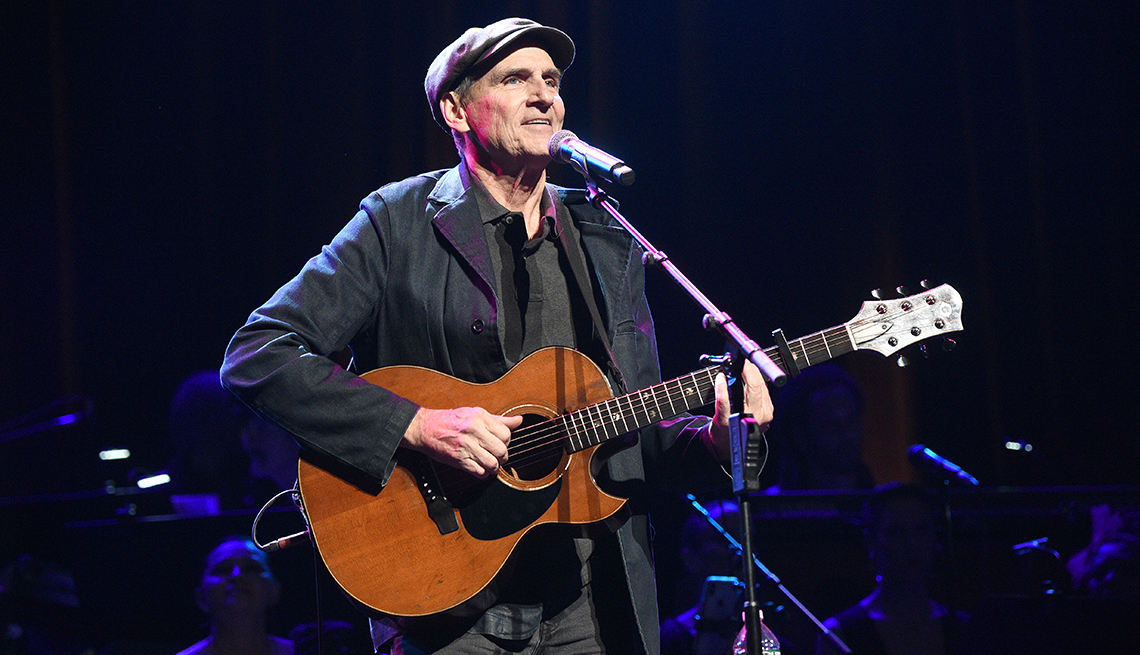 James Taylor playing his guitar onstage during a performance in New York City