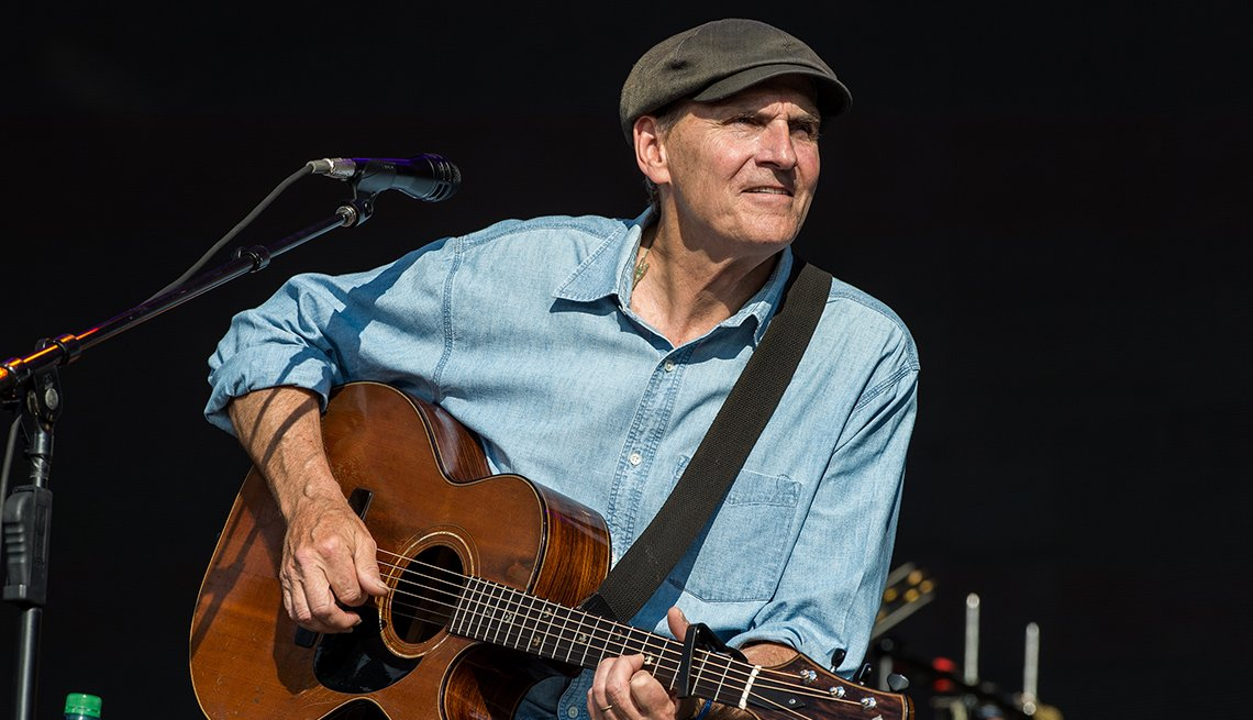 James Taylor performing on stage with his guitar