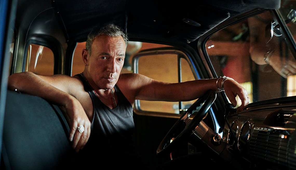 bruce springsteen poses in the drivers seat of one of his antique cars