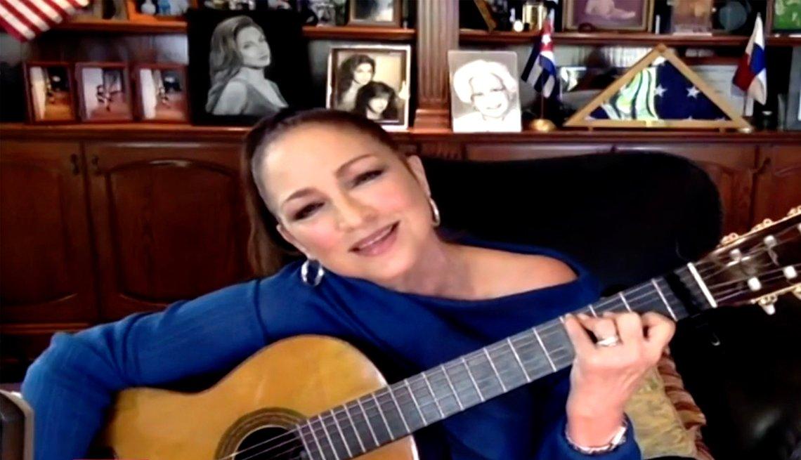 Gloria Estefan performing virtually with an acoustic guitar