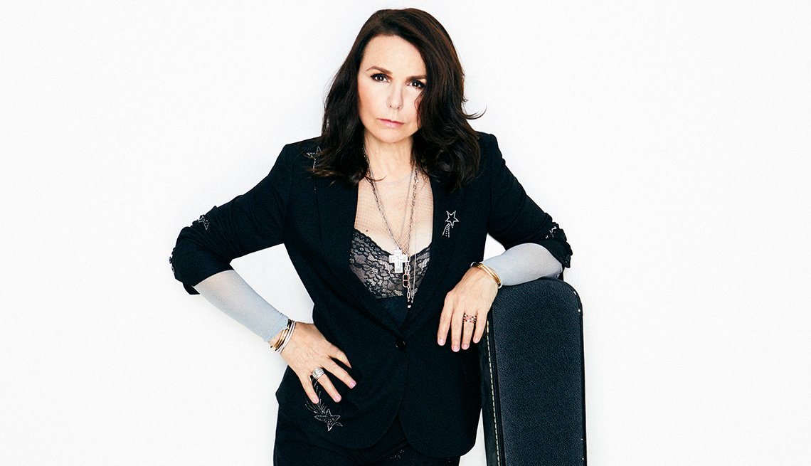 Patty Smyth standing next to a guitar case