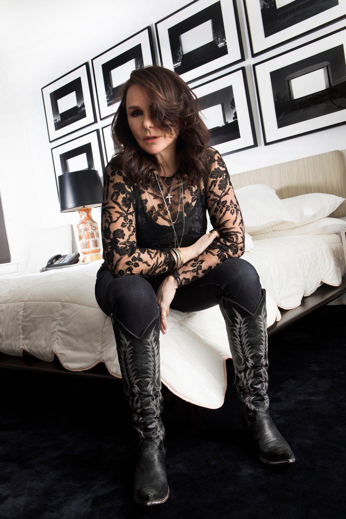 Singer Patty Smyth sitting on a bed