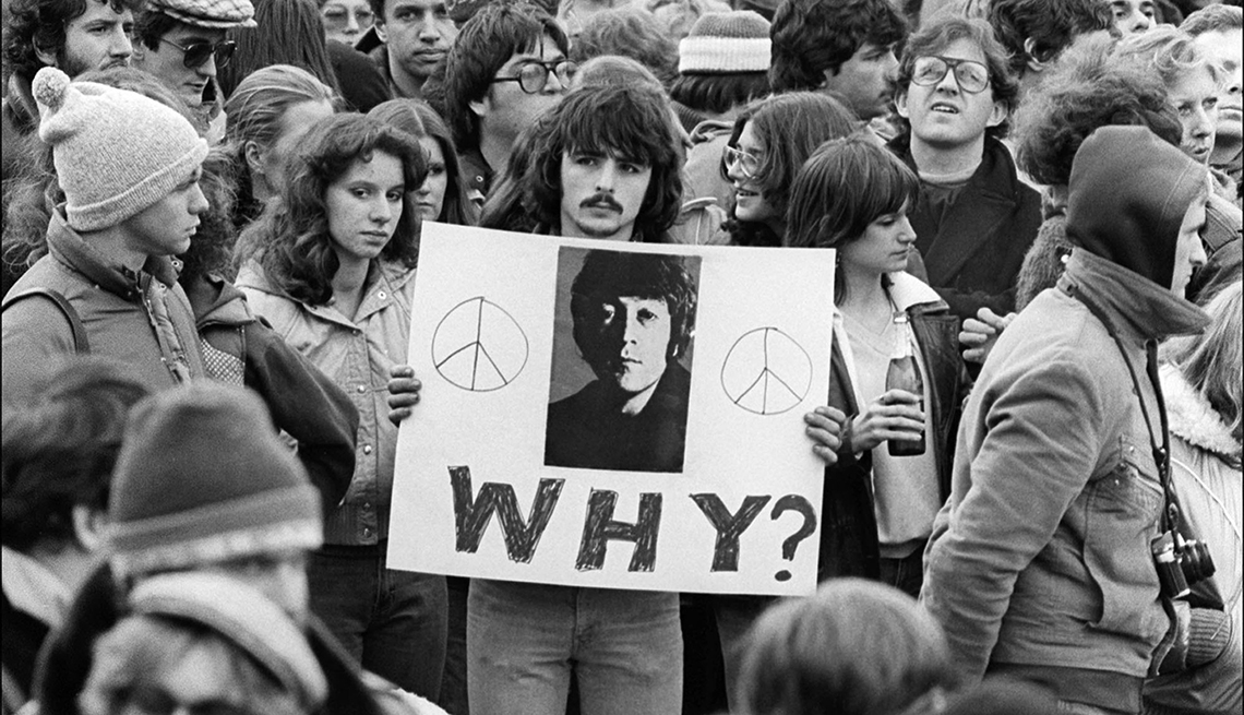 closeup of man holding sign with a photo of john lennon and the word why with a question mark the man is in a crowd at lennon memorial vigil shortly after he was killed