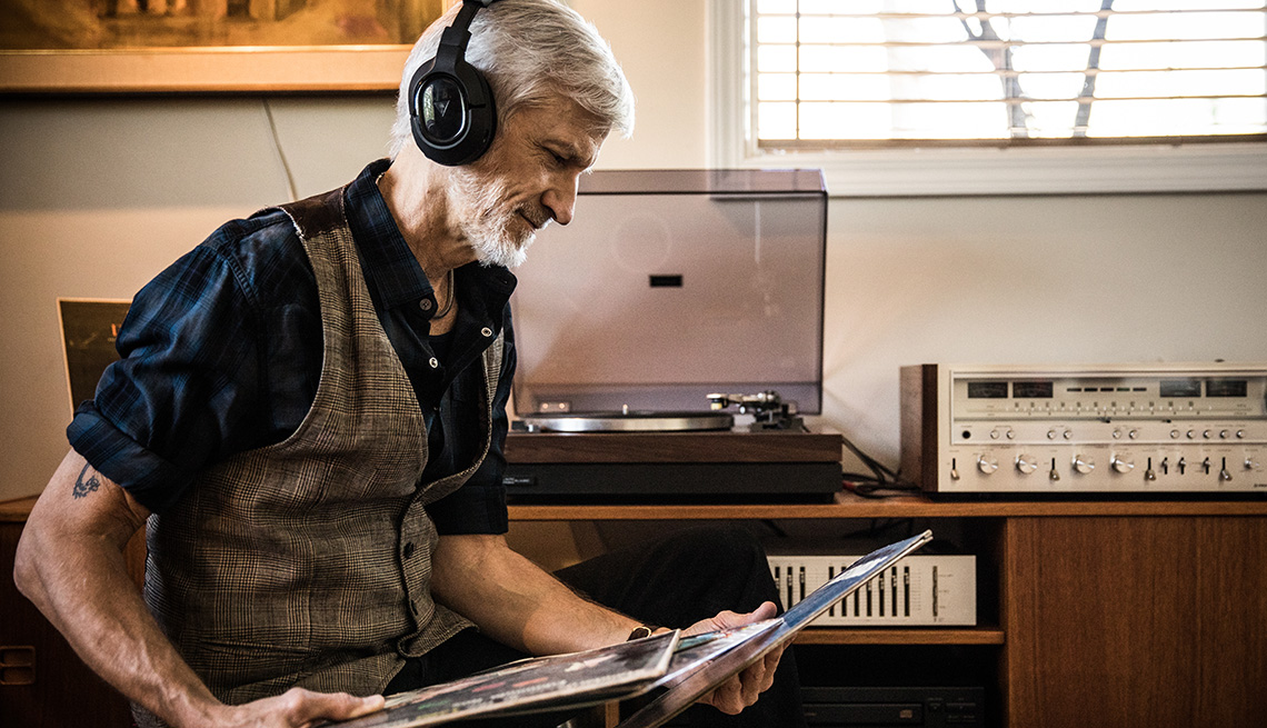A man wearing headphones listening to vinyl records