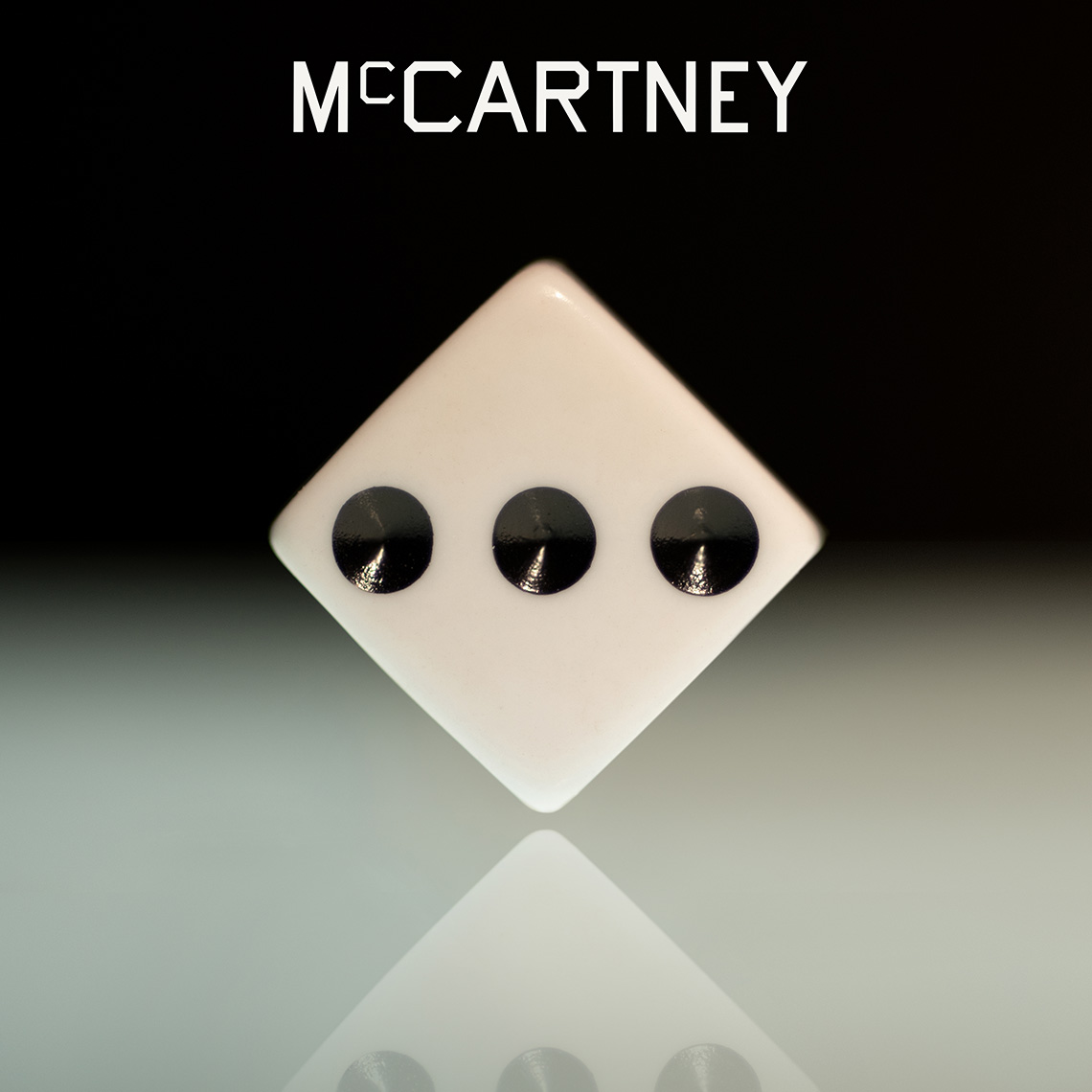 The album cover art for McCartney III, a rendering of a die balanced on one point with three dots facing the viewer