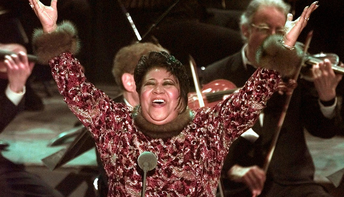 Aretha Franklin raises her arms in the air after performing Nessun Dorma at the 40th Annual Grammy Awards in New York