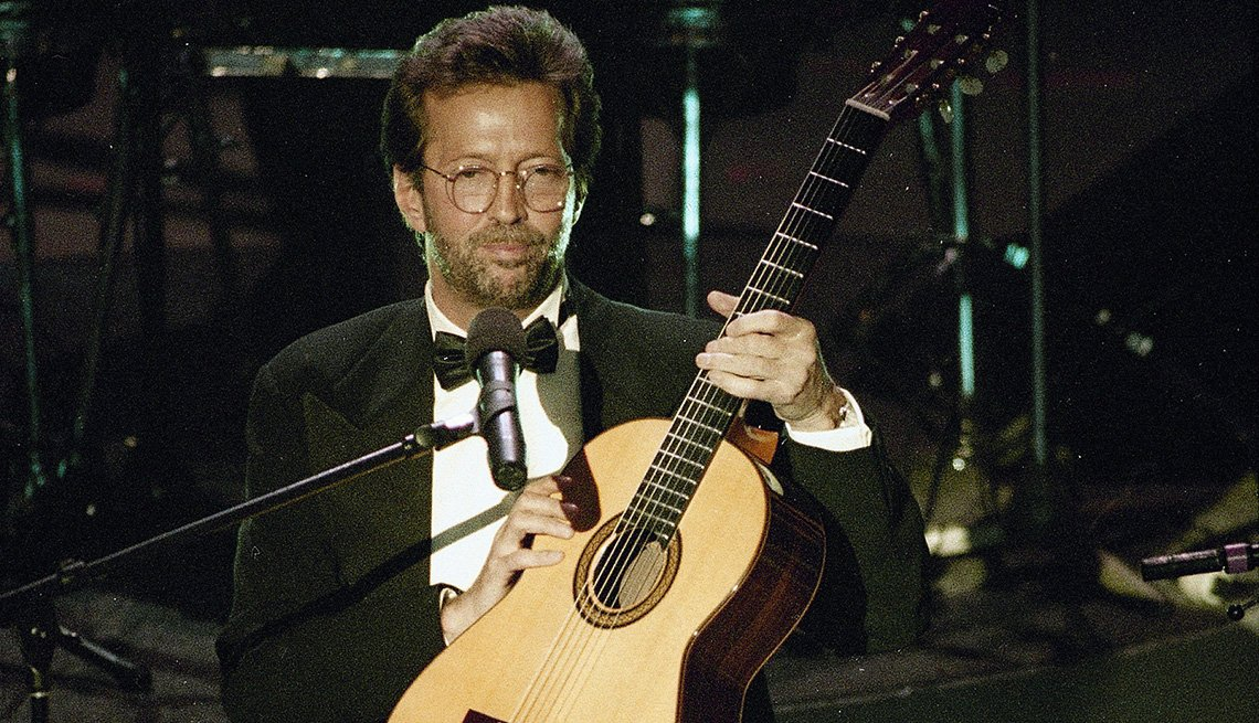 Eric Clapton holds his guitar onstage during his performance of Tears in Heaven at the 35th annual Grammy Awards