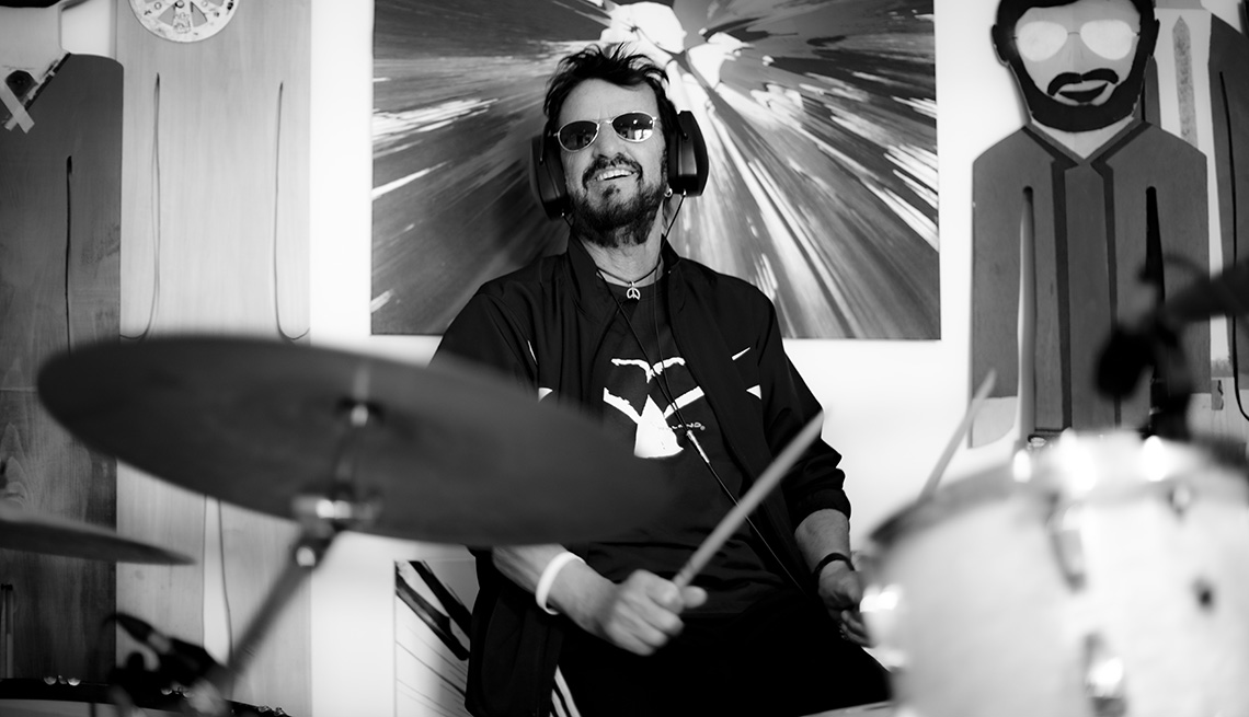 A black and white photo of Ringo Starr sitting at a drum set