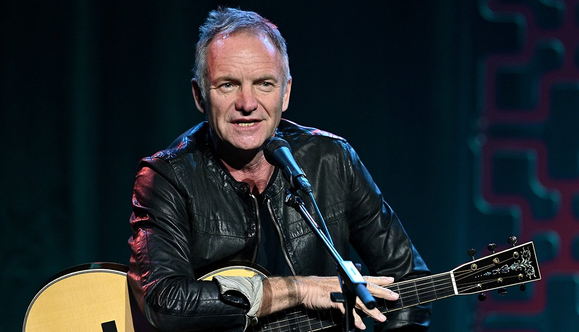 Sting on stage with an acoustic guitar talking into a microphone