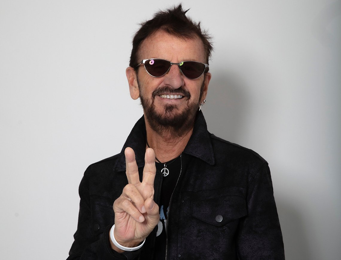 Ringo Starr wearing sunglasses while giving the peace sign