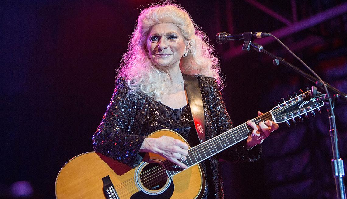 Judy Collins sosteniendo su guitarra durante una actuación en el escenario.
