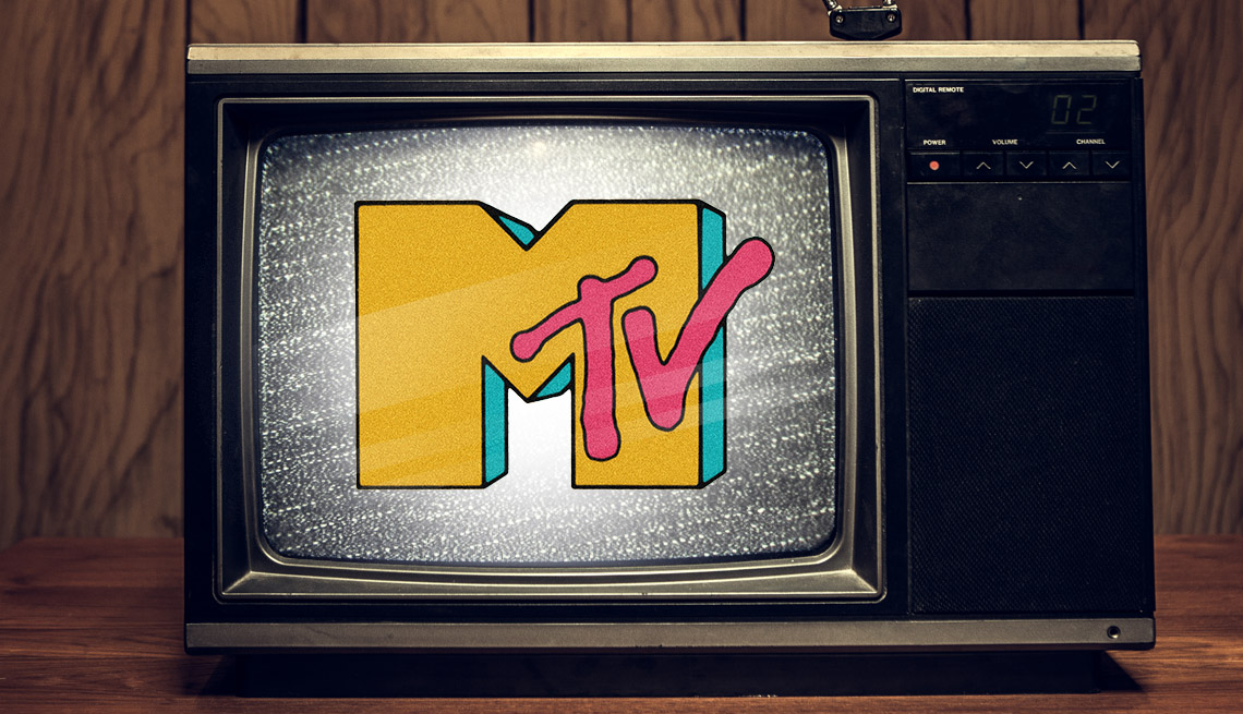 a tv from the eighties on a desk in a wood paneled room with static on the screen and the original m t v logo