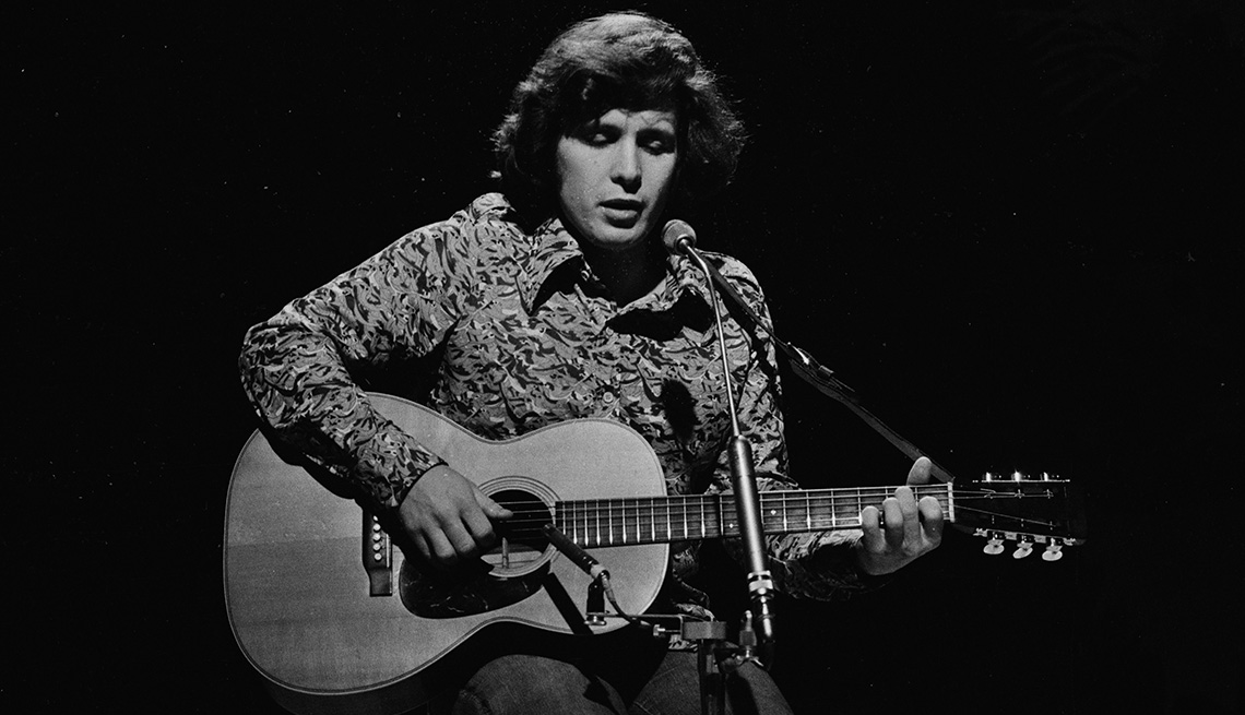 Don McLean playing his guitar during a performance in 1972