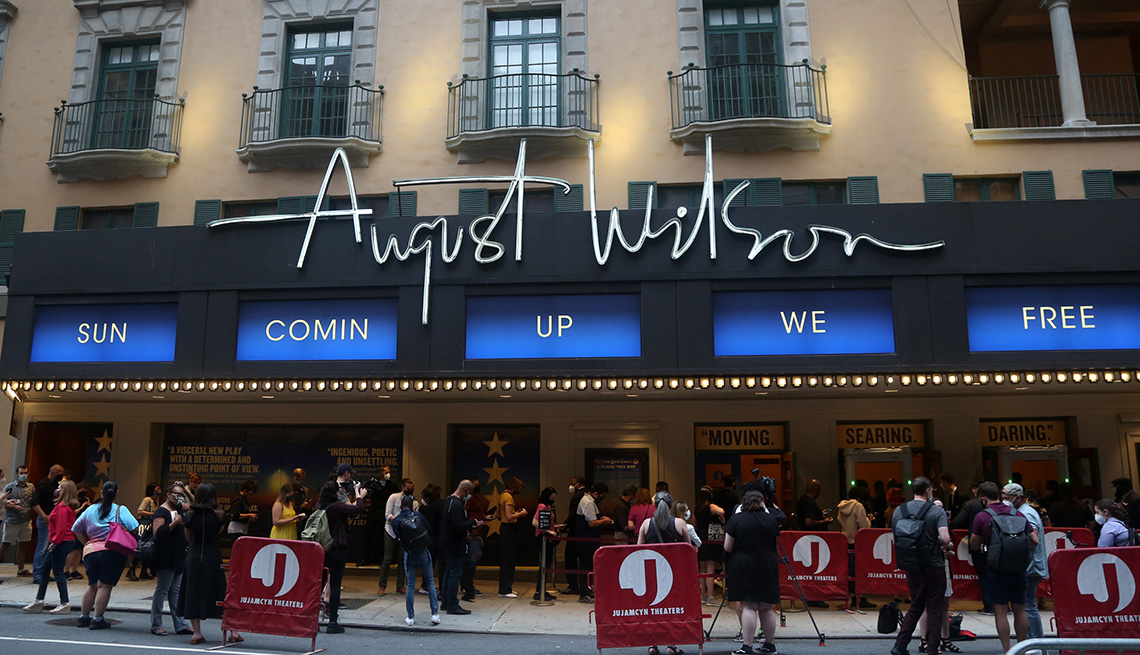 Signage and a crowd on Broadway outside of The August Wilson Theatre
