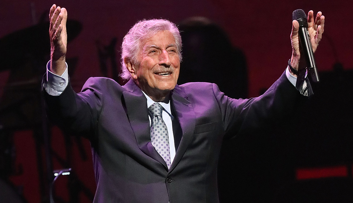 Tony Bennett raises his arms in the air during a performance onstage