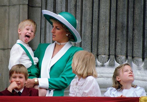 El Príncipe Harry saca la lengua mientras que siendo sostenido por su madre, la princesa Diana, en el balcón del Palacio de Buckingham, junio de 1988.