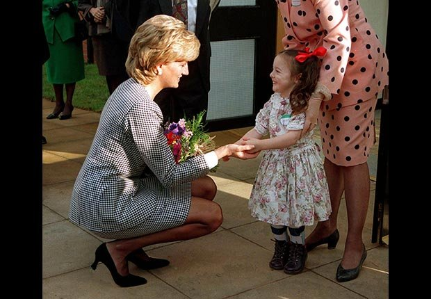 Princess Diana holding hands with a young girl in 1995. (Jayne Fincher/Getty Images)