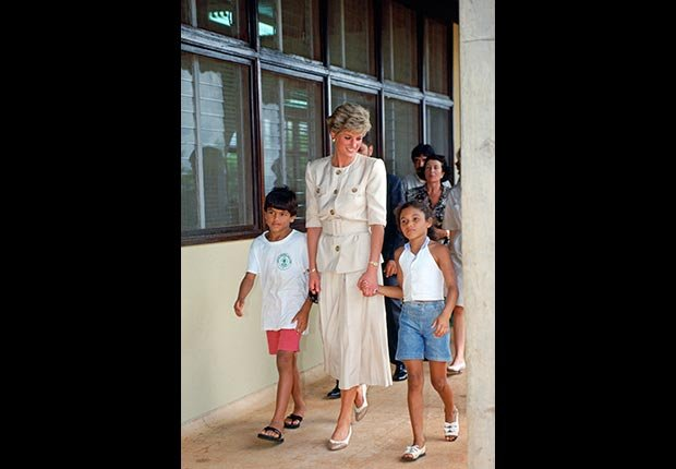 Princesa Diana de la mano con dos niños durante una visita a una escuela en Carajás, Brasil, en abril de 1991.