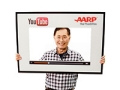 George Takei holds a YouTube poster, AARP On The Web (Michel DeAscentiis)